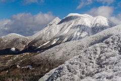 Mt. Mimata with Snow and Blue Skies. One of the distinctive peaks of Japan`s Aso-Kuju National Park covered in snow on a sunny day Royalty Free Stock Photo