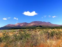 Mt. Ngauruhoe - Mt. Doom in New Zealand, volcanic drive on south island. Mt. doom in new zealand beautiful view of the volcano under the blue summer-sky royalty free stock photography