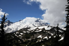 Mt. Rainier, Washington. Snow-covered Mt. Rainier, Washington in background of large moving white cloud, surrounded by blue skies Royalty Free Stock Photography