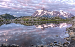 Mt. Shuksan and Artist Ridge Tarn. Mt Shuksan and colorful sunset clouds reflected in a tarn on Artist Ridge in Mt. Baker-Snoqualmie National Forest, Washington Stock Image