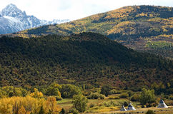 Mt. Sneffles and Teepees. Autumn colors and snow covered 14,000'peak mt sneffles with three painted teepees in foreground royalty free stock photography