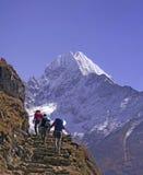 Mt. Thamserku et trekkers Photographie stock