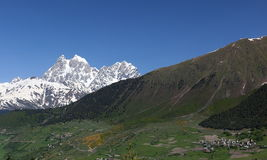 Mt. Ushba and Village Mulakhi. Svaneti. Georgia. Royalty Free Stock Photography