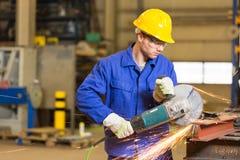 Métal en acier de coupe de travailleur de la construction avec la broyeur d'angle Photographie stock