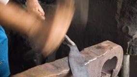 Métal travaillant de forgeron avec le marteau banque de vidéos