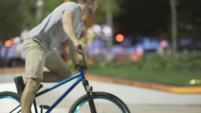 MTB bicycle rider does various tricks while riding in skatepark . Extreme Sports, rider does barspin to three sixty trick at nigh stock video footage