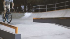 MTB bicycle rider does various tricks while riding in skatepark . Extreme Sports, rider does barspin trick at nigh stock video