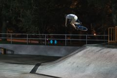 MTB bicycle rider does various tricks while riding in skatepark . Extreme Sports, rider does tabletop trick at night Royalty Free Stock Images
