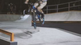MTB bicycle rider does various tricks while riding in skatepark . Extreme Sports, rider does three sixty trick at nigh stock footage