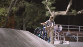 MTB bicycle rider does various tricks while riding in skatepark . Extreme Sports, rider does tabletop trick at nigh. MTB bicycle rider does various tricks while stock video