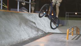 MTB bicycle rider does various tricks while riding in skatepark . Extreme Sports, rider does wallride trick at nigh stock footage