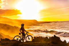 MTB Mountain Biking Cyclist looking at sunset view. MTB cyclist mountain biking woman cycling looking at view on bike trail on coast at sunset. Person on bike by royalty free stock image