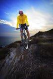 Mtb de la bici del moutain del montar a caballo del hombre joven en la duna de la tierra contra el cielo oscuro Fotos de archivo libres de regalías