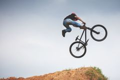 Mtb dirt rider doing trick on a jump. Against sky royalty free stock photography