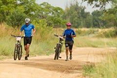 MTB Mitfahrer, die nahe bei Fahrrad laufen Lizenzfreie Stockfotografie