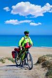MTB-Radfahrer-Fahrrad, das auf einen Strand mit Korb bereist Stockbilder