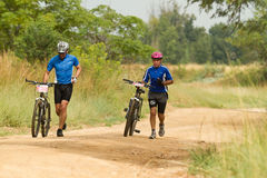 MTB Riders running next to bicycle Royalty Free Stock Photography
