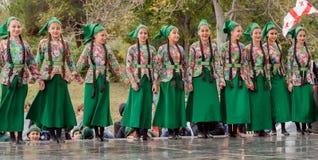 MTSKHETA, GEORGIA - 14-ОЕ ОКТЯБРЯ: Неопознанные счастливые девушки в традиционных грузинских платьях танцуя на этапе партии Стоковые Изображения RF