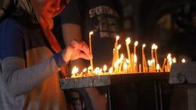 MTSKHETA, GEORGIA - 15 de julio de 2018: La mano de la mujer lleva a cabo y pone una vela en la iglesia La gente en el templo rue
