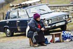Mtskheta, Georgia, el 18 de noviembre de 2014: Una mujer mayor que se sienta en el franco fotos de archivo