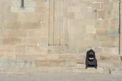 Lonely old monk in black clothes sits on stairs near the old orthodox cathedral in town Mtskheta near Tbilisi, Georgia royalty free stock photos