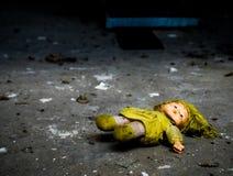 Muñeca abandonada en piso sucio Imagenes de archivo