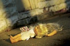 Muñeca abusada que miente en la tierra Foto de archivo libre de regalías