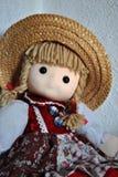 Muñeca bonita con una sentada del sombrero de paja imagen de archivo libre de regalías