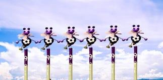 Muñeca-como la pequeña abeja que se coloca en línea en un fondo del cielo Fotografía de archivo