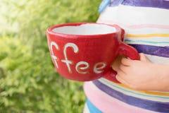 Muñeca de cerámica que sostiene la taza de café Imagenes de archivo
