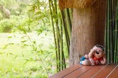Muñeca de cerámica sonreída del muchacho en postura de descanso foto de archivo