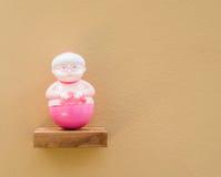 Muñeca de la mujer mayor, fondo del color de la cáscara de huevo fotografía de archivo libre de regalías