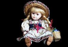 Muñeca de la porcelana en fondo oscuro Foto de archivo