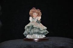 Muñeca de la porcelana - muchacha tímida en un vestido elegante imagen de archivo