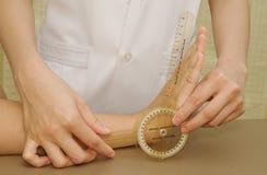Muñeca de los pacientes del examen del fisioterapeuta con el goniómetro Imagen de archivo