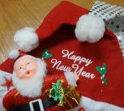 Muñeca de Santa Claus y mensaje blanco de la Feliz Año Nuevo en el sombrero rojo de Papá Noel Foto de archivo libre de regalías