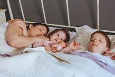 Muñeca del abarcamiento de la niña que miente sobre la cama Foto de archivo libre de regalías
