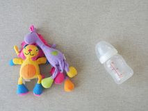 Muñeca del juguete del bebé y botella de leche vacía Imagenes de archivo