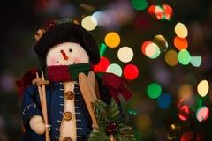 Muñeca del muñeco de nieve con los esquís y las luces de la Navidad Fotos de archivo libres de regalías