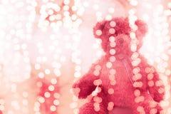 Muñeca del oso de peluche en la línea de iluminación rosa del bokeh brillante para el fondo de la Navidad o de la Feliz Año Nuevo fotos de archivo libres de regalías