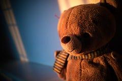 Muñeca del oso de peluche que se sienta al lado de la ventana con la luz de la puesta del sol poli Fotografía de archivo