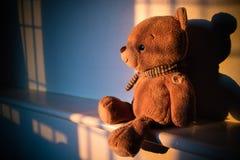 Muñeca del oso de peluche que se sienta al lado de la ventana con la luz de la puesta del sol poli Fotos de archivo