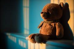 Muñeca del oso de peluche que se sienta al lado de la ventana con la luz de la puesta del sol poli Fotografía de archivo libre de regalías
