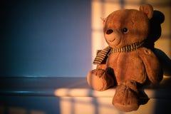 Muñeca del oso de peluche que se sienta al lado de la ventana con la luz de la puesta del sol poli Foto de archivo