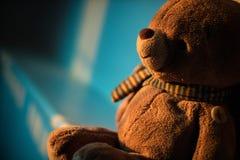 Muñeca del oso de peluche que se sienta al lado de la ventana con la luz de la puesta del sol poli Imagen de archivo