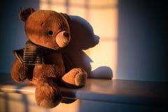 Muñeca del oso de peluche que se sienta al lado de la ventana con la luz de la puesta del sol poli Imagen de archivo libre de regalías