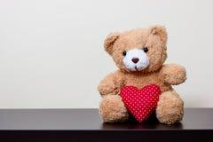 Muñeca del oso y corazón rojo imagenes de archivo