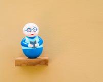 Muñeca del viejo hombre, fondo del color de la cáscara de huevo foto de archivo