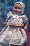 Muñeca del vintage con el casquillo blanco en la cabeza que se sienta en la trona de madera imagen de archivo