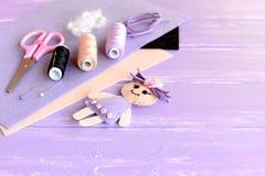 Muñeca divertida adornada con los botones, sistema del hilo, aguja, pernos, tijeras, pedazos planos de fieltro en fondo de madera fotos de archivo